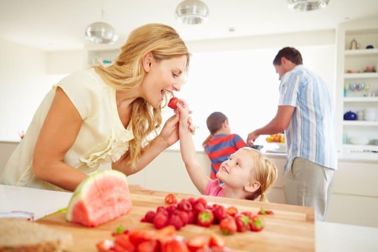 Mor og barn spiser friske jordbær
